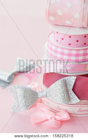 Rolls of gift ribbon stacked on a pink background