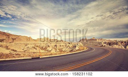 Vintage toned desert road just before sunset travel concept USA.