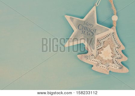 Blue and white christmas with star and christmas tree on blue wooden background, retro toned
