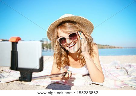 Beautiful girl in sunglasses taking selfie on beach