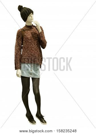 Female mannequin wearing sweater bobble cap and blue denim skirt isolated on white background.