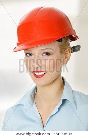 Young female engineer in red helmet