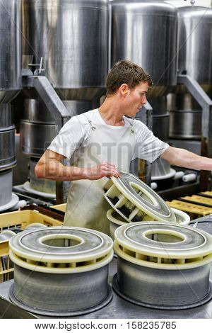 Cheesemaker Putting Young Gruyere Comte Cheese At Forms In Dairy