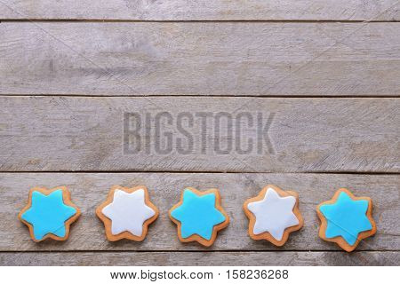 Tasty glazed cookies for Hanukkah on wooden table