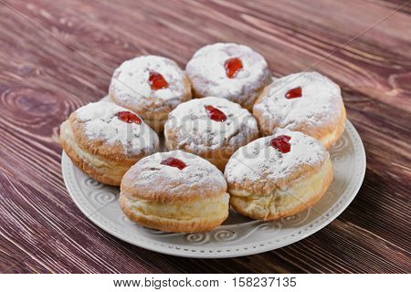 Plate with tasty donuts for Hanukkah on wooden table, closeup