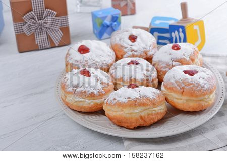 Plate with tasty donuts for Hanukkah on light wooden table, closeup