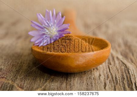 Blue Chicory Flower And Full Wooden Spoon Of Powder  Instant Chicory On Old Wooden Table