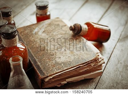 Old book with glass bottles on wooden background, closeup