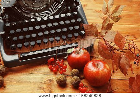 Autumn composition with old typewriter on wooden background