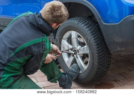 Young man exchanging the car tires. From summer tires on winter tires on his car.