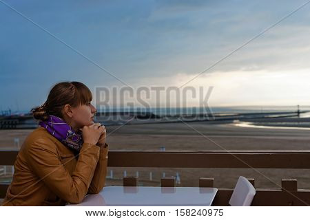 Young girl sitting on the balcony with a view on the embankment of Grande plage at English Channel in Trouville-sur-Mer or Trouville in Calvados department of Normandy region France. At sunset