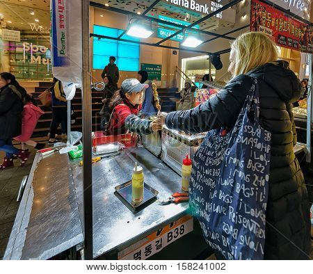 Girl Buying Street Food At Myeongdong Street Market In Seoul