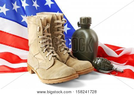 Pair of combat boots, grenade, canteen and USA flag on white background