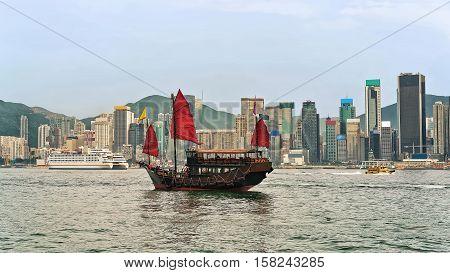 Junk Boat At Victoria Harbor In Hong Kong At Sundown