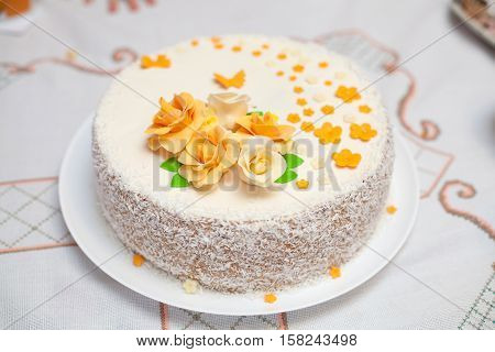 White mastic cake decorated with orange flowers, closeup