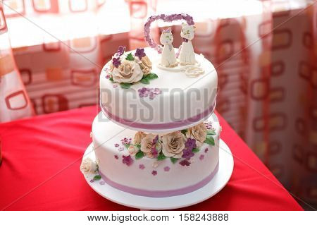 White wedding mastic cake decorated with beige flowers and cat figures, closeup