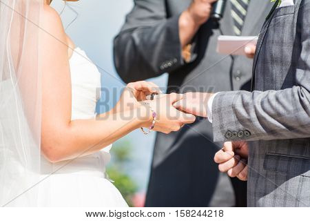 A bride puts the ring on the groom at a wedding ceremony