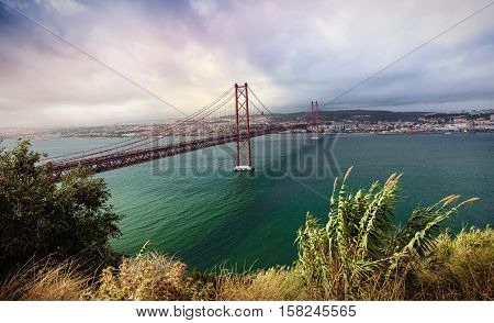Hanging 25th of April Bridge connecting Lisbon to the north and Almada on the south side of the river Tagus. View on the center of Lisbon