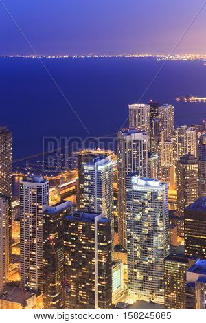 Chicago skyline aerial view with skyscrapers over Lake Michigan with cloudy sky at dusk.