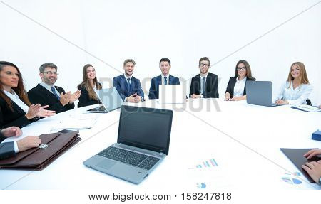 Side view of smilimg business team, sitting at a round table on