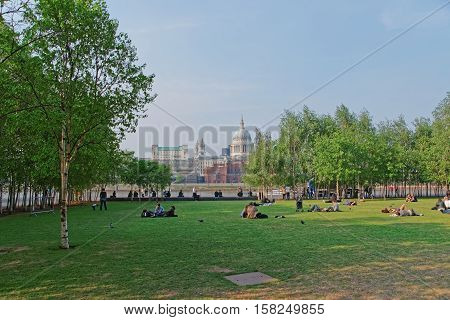 People Relaxing In Park At Bankside And St Paul Cathedral