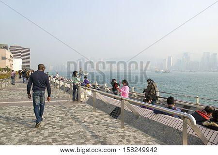 People Walking At Embankment Of Victoria Harbor In Hong Kong