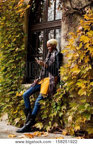 Modern young african american woman holding mobile hone and smiling at autumn outdoor