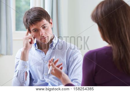 Depressed Young Man Talking To Female Counsellor
