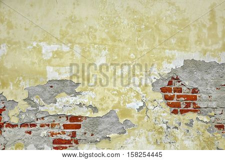 Old Brick Wall With Damaged Shabby Yellow Plaster Layer Background. Grunge Brickwall With Rundown Stucco Horizontal Texture. Lime Wash Distressed Vintage Stonewall Chipped Urban Surface
