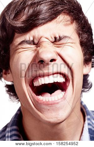 Face close up of young hispanic man screaming over white background - pain concept