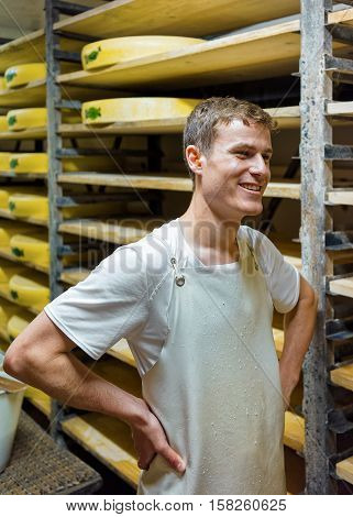 Worker And Aging Cheese At Ripening Cellar Franche Comte Creamery