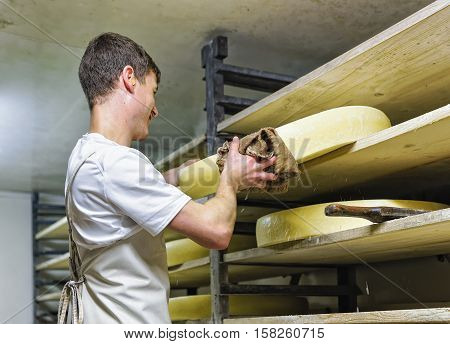 Worker At Ripening Cellar With Aging Conte Cheese At Creamery