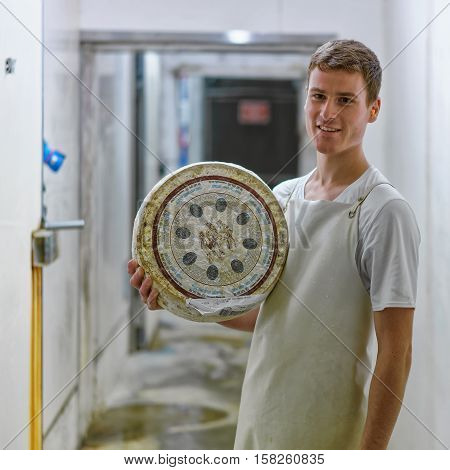Worker Holding A Wheel Of Cheese At Storehouse