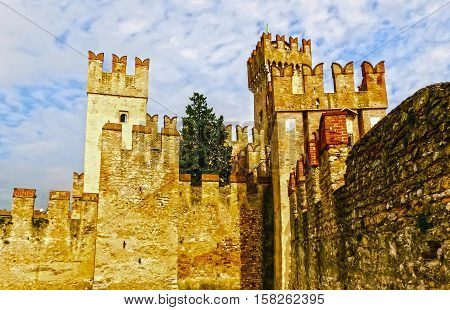 Sirmione, Italy - Scaliger Castle. The famous castle of Sirmione and its small port are an uncommon example of a fortress used as a port. The building of this complex started in 1277 by Mastino della Scala.