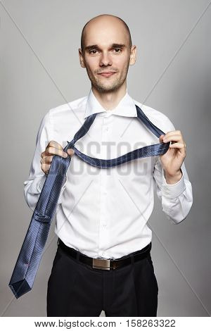 Takes Off A Necktie