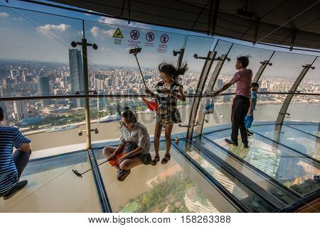 SHANGHAI CHINA - AUGUST 29 2016: An unidentified people take selfie photo on transparent glass floor of TV Oriental Pearl Tower against Huangpu river and quay in Shanghai China on August 29 2016.