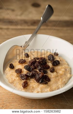 Bowl Of Porridge And Raisins On Wooden Background