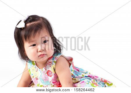 Cute baby girl sitting in studio on white board.