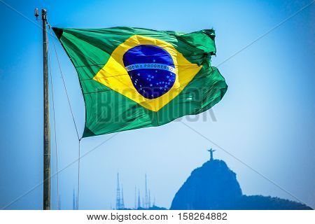 Brazilian flag on the background of Christ the Redeemer, Art Deco statue of Jesus Christ in Rio de Janeiro, Brazil