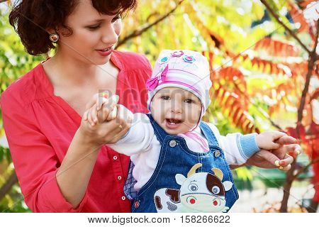 A happy family. Mom and year-old daughter playing in the park