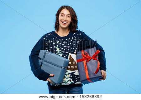 Young beautiful brunette girl in cosy knited sweater smiling holding gift boxes over blue background. Copy space.