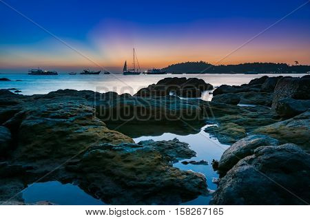 Colorful dark twilight sea and sky after sunset with sailboat motorboat docking in the calm sea in high season with rocks and small colonial of Lichen covered