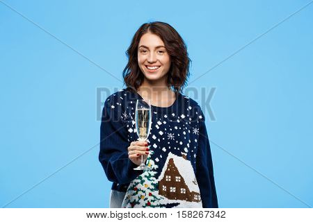 Young cheerful beautiful brunette girl in cosy knited sweater smiling holding glass of champagne over blue background. Copy space.