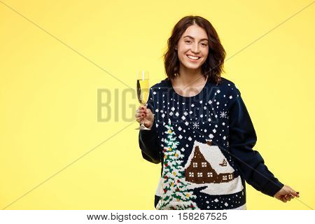 Young cheerful beautiful brunette girl in cosy knited sweater smiling holding glass of champagne over yellow background. Copy space.