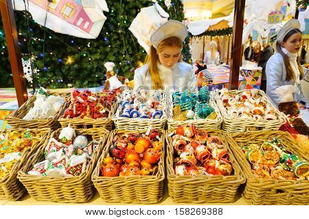 MOSCOW - NOVEMBER 22: Saleswoman behind the counter at the New Year Fair in GUM on November 22 2016 in Moscow.