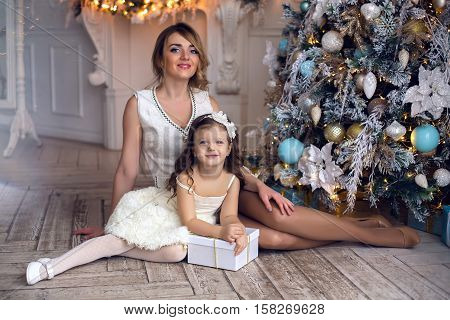 mother and daughter three years sitting at the Christmas tree decorated with toys and gifts