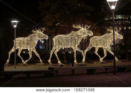 Side view of a herd of Christmas moose made of led light Nybrokajen Stockholm Sweden