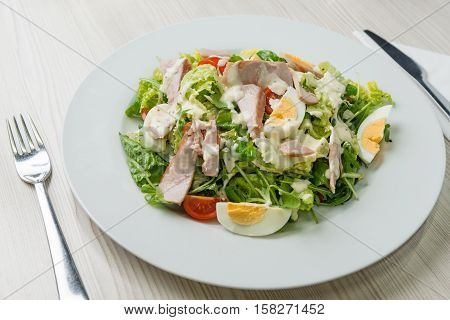 Nutritious vegetable salad with boiled egg slices and salmon