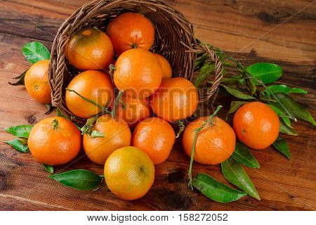 Tangerines basket scattered fruits on woden table