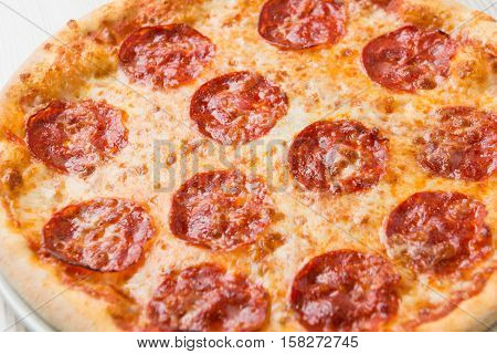 Detail of salami pizza on the table